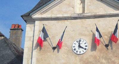 Drapeau français et horloge sur un bâtiment